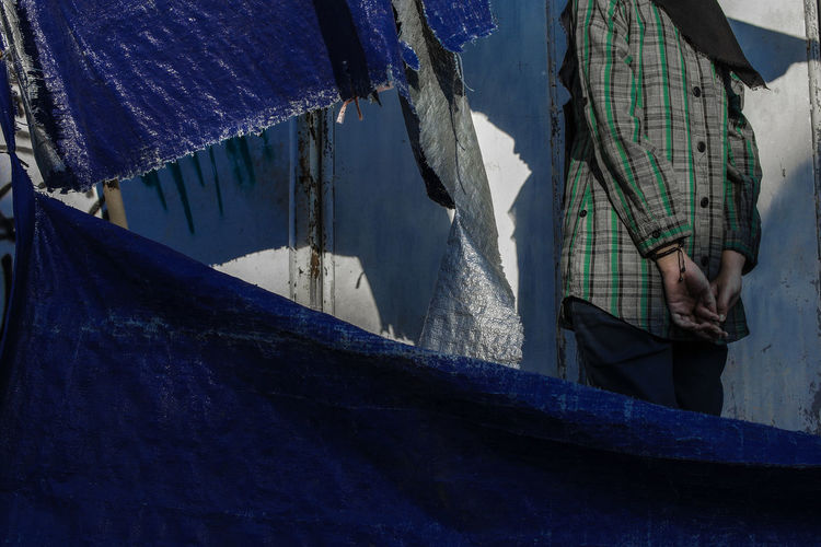 Midsection of woman standing by wall and tarpaulin