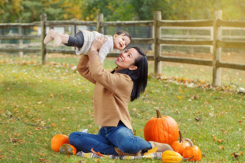 Mother picking up daughter while sitting on land during autumn