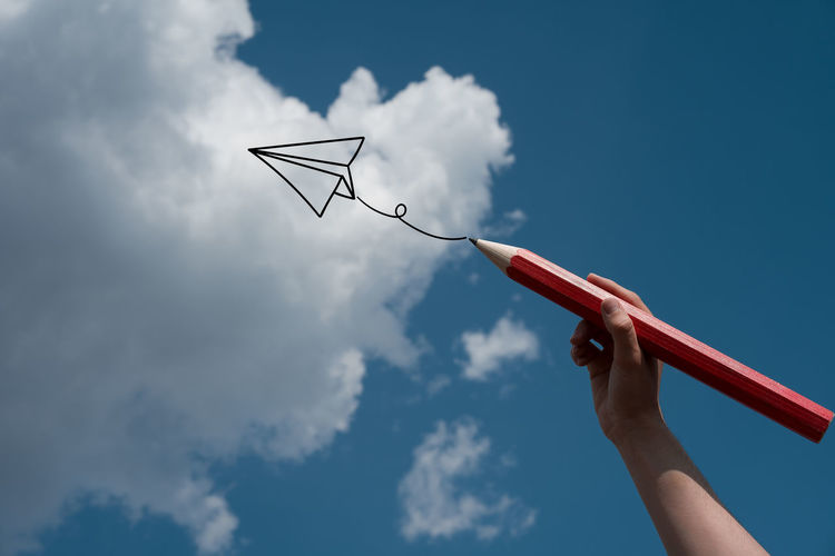 Digital composite image of hand drawing airplane against sky