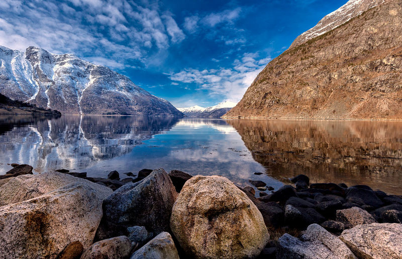 Water Rock Scenics - Nature Tranquility Tranquil Scene Sky Solid Lake Beauty In Nature Nature Rock - Object Cloud - Sky Reflection Mountain No People Non-urban Scene Idyllic Day Blue Eidfjord