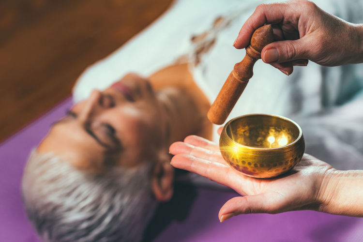Cropped hands of woman playing singing bowl for customer in spa