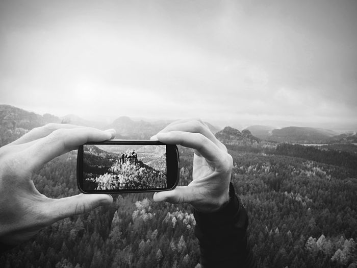 Man takes photos with phone on rock empire. dreamy foggy mountains, spring  misty sunrise in valley
