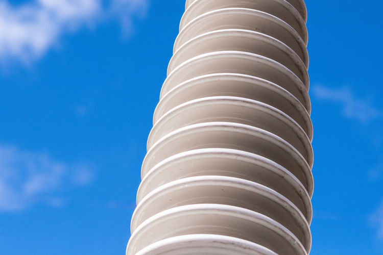 Polymer ceramic insulator with high voltage. Dangerous engineering facility. Close up. Sky Cloud - Sky Low Angle View Architecture Built Structure No People Day Pattern Nature Tower Blue Building Exterior White Color Outdoors Industry Tall - High Architectural Feature Sunlight Travel Architectural Column Skyscraper