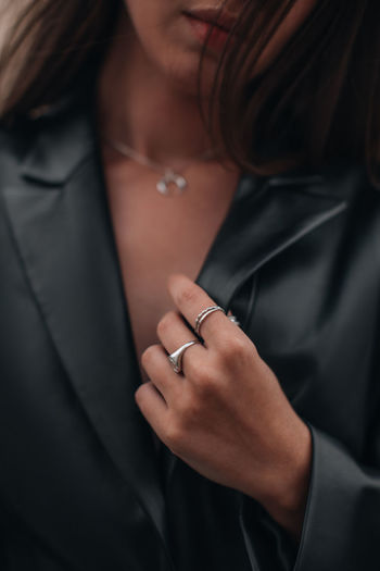 Female hands in a black stylish leather jacket and silver accessories on a female body. jewelry