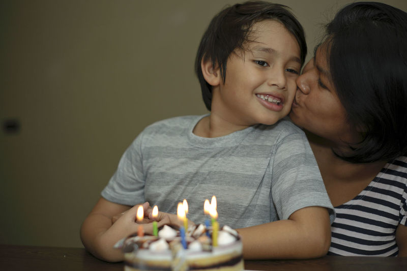Mother and son celebrating birthday kissing Celebration Family Happiness Happy Happy People Love Mother And Son Birthday Blowing Candles Bonding Candle Celebrating Child Childhood Close-up Headshot Indoors  Kid Kissing Love Real People Togetherness
