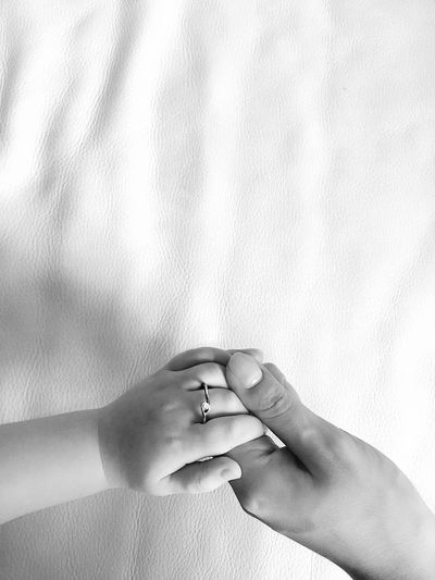 Cropped Hand Of Parent Holding Child Hand On Bed