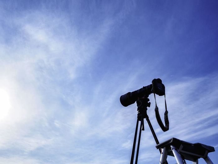 Low angle view of camera against blue sky
