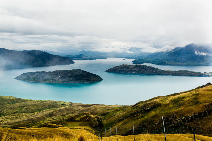 View of Lake Wanaka New Zealand Landscape Beauty In Nature Cloud - Sky Day Environment Idyllic Landscape Mountain Mountain Range Nature No People Non-urban Scene Outdoors Plant Scenics - Nature Sky Tranquil Scene Tranquility Turquoise Colored Volcanic Crater Wanakalake Water