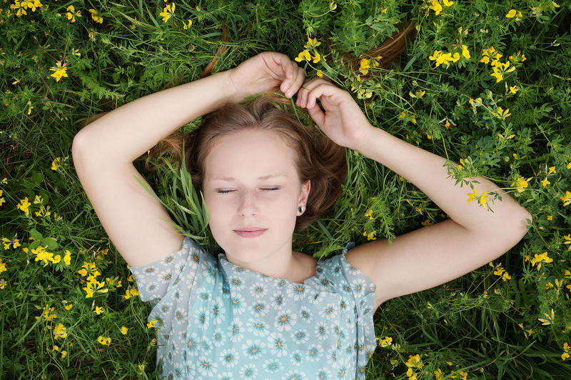 Directly Above Shot Of Young Woman Relaxing On Field At Park