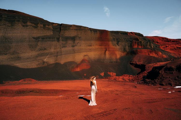 Full length of woman standing on soil against rock mountain