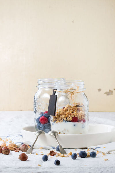 Glass jar with homemade granola and yogurt served with nuts, raspberries and blackberries over white textile Berries Bluebarry Breakfast Food Food Photography Freshness Glass Jar Granola Healthy Eating Homemade Linen Texture Mason Jar Mix Morning Muesli Nuts Raspberry Sweet Sweet Food Table Textile White Background Yoghurt Yogurt