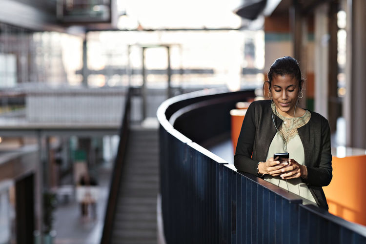 Portrait of young woman using phone on railing