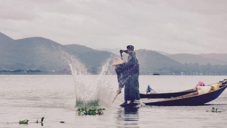 Man splashing water in river with oar against sky