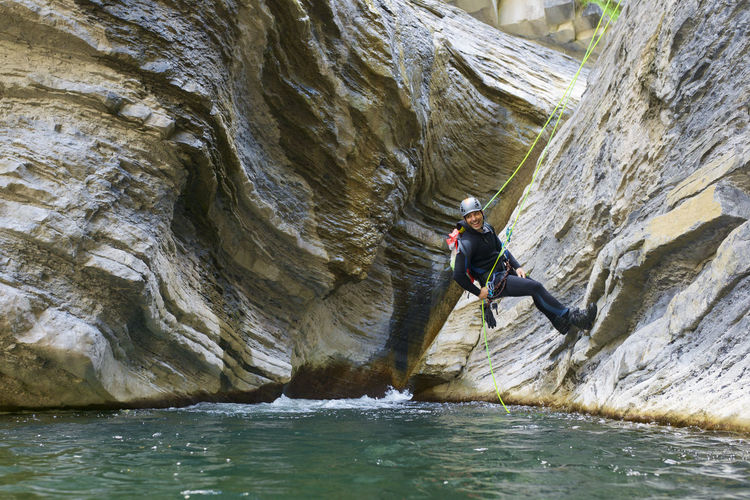 Man standing on rock formation in water