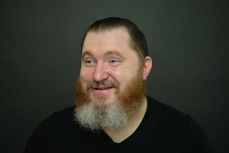 Portrait of a smiling man against black background
