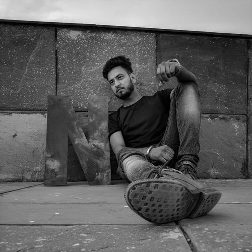 Low angle view of man sitting by wall on footpath
