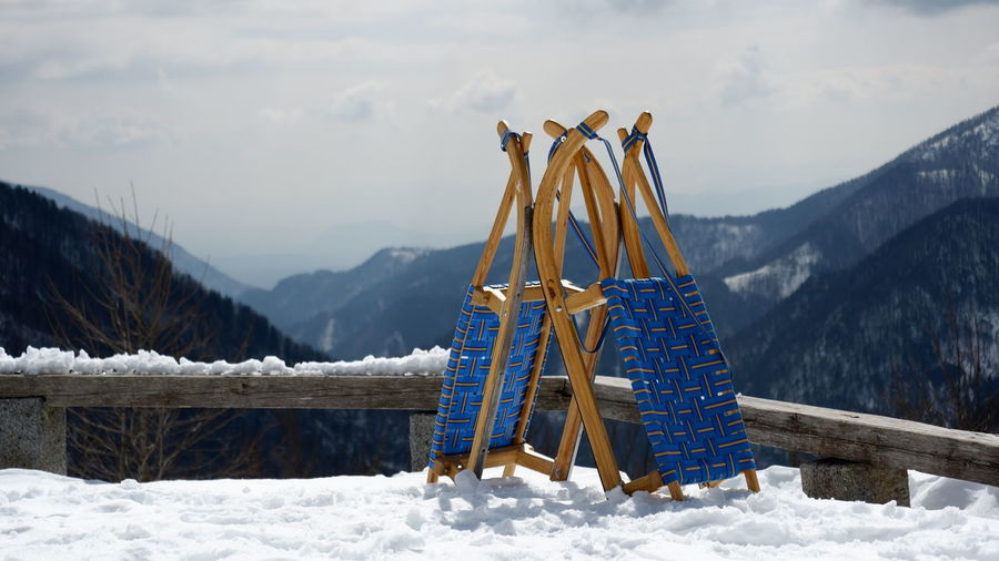 Traditional windmill on snowcapped mountain against sky