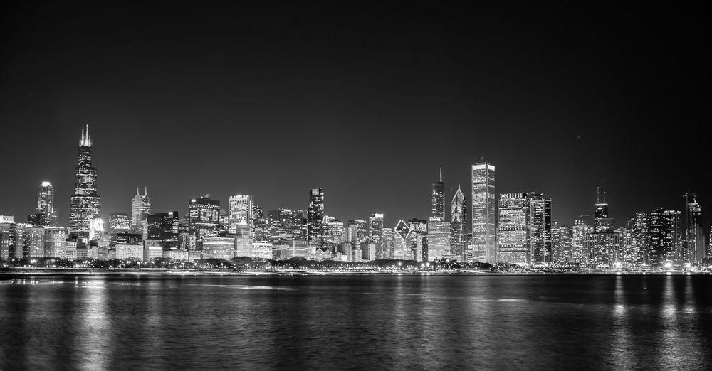River Against Illuminated Cityscape At Night
