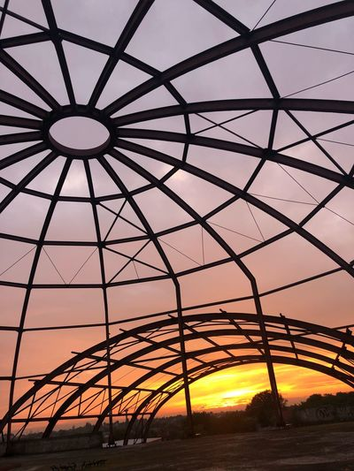 Low angle view of silhouette metallic structure against sky during sunset