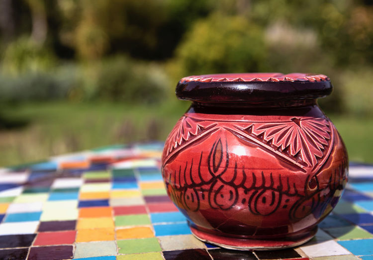 a very imaginative garden space outside of Marrakech, Morocco with beautiful and colourful objects blending with the garden Garden Park Colorful ArtWork Trees Path Imaginative Marrakech Morocco Anima Garden Textured  Focus On Foreground Pattern Table Close-up No People Multi Colored Still Life Creativity Art And Craft Red Design Day Checked Pattern Container Lighting Equipment Outdoors Craft Food And Drink Lantern Electric Lamp