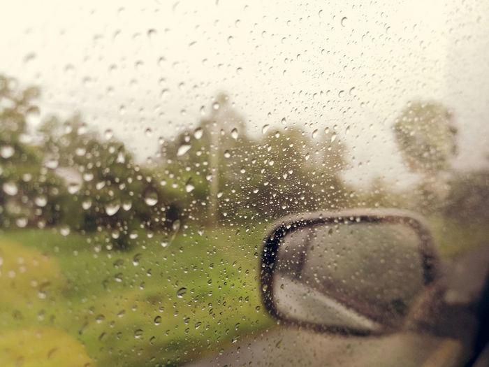 Close-up portrait of wet glass window