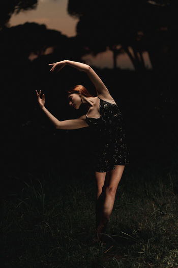 Midsection of woman with arms raised on field at night