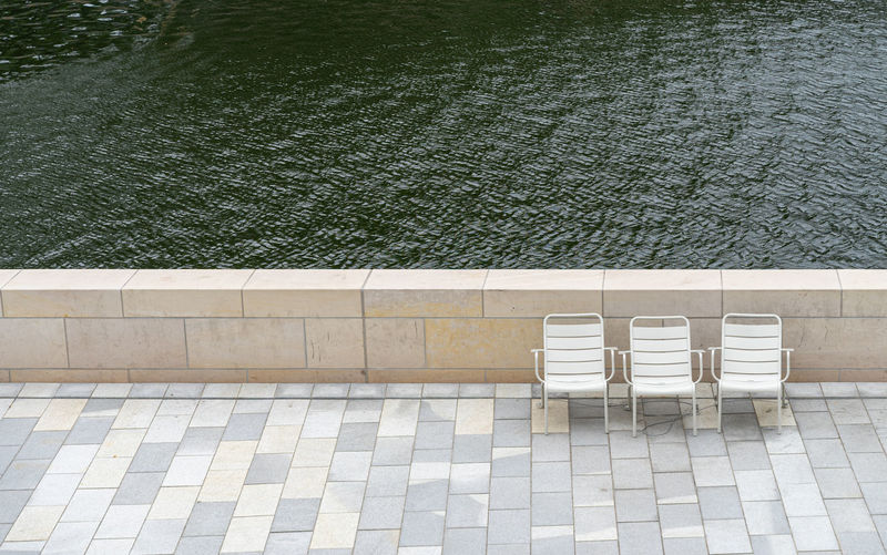 High angle view of chairs by lake