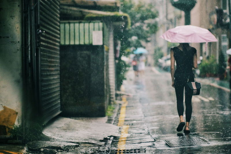 Rear view of woman with umbrella walking on footpath in rain