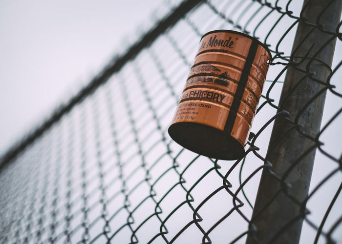 Low angle view of tin can hanging on chainlink fence