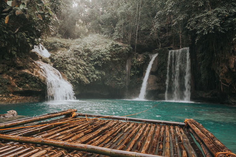 Wooden raft on river against waterfall at forest