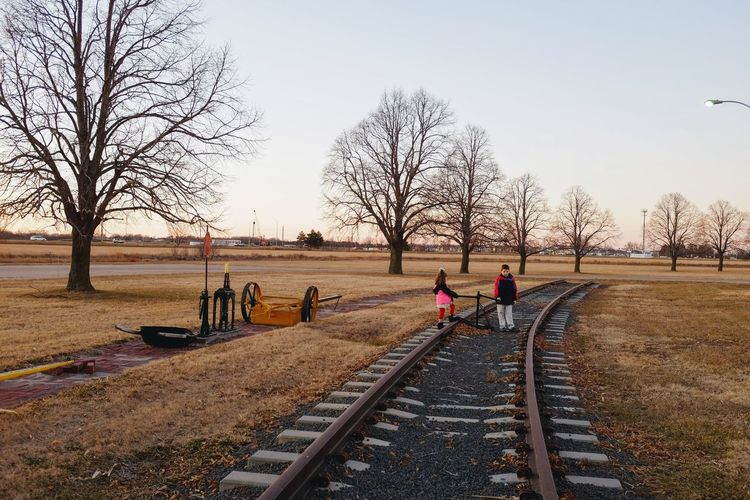 Siblings on railroad track against sky during sunset
