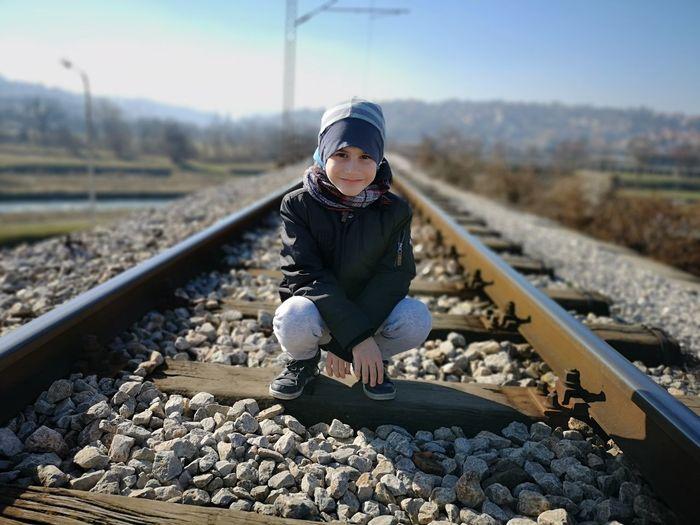 Portrait of cute boy crouching on railroad track