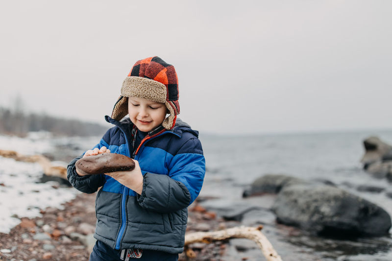 Smiling boy looking at rock while standing on shore against clear sky