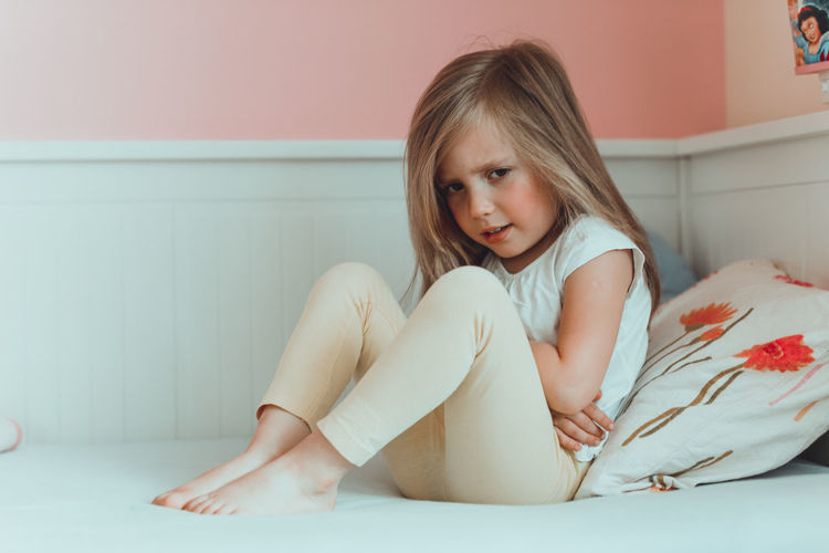 Girl With Stomachache Sitting On Bed At Home