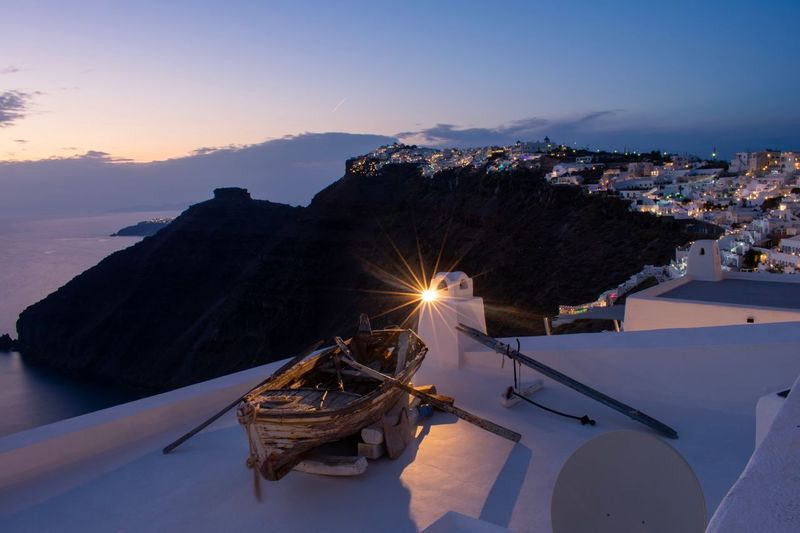 Santorini's beautiful view Clouds Lights Houses Mountain Range Summer EyEmNewHere Santorini Imerovigli Boat EyeEm Selects Sky Architecture Water Built Structure Building Exterior Illuminated Nature Sea Transportation City Sunset Dusk Mode Of Transportation Outdoors No People High Angle View Cityscape