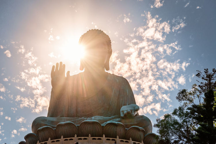 Low angle view of buddha statue against sky