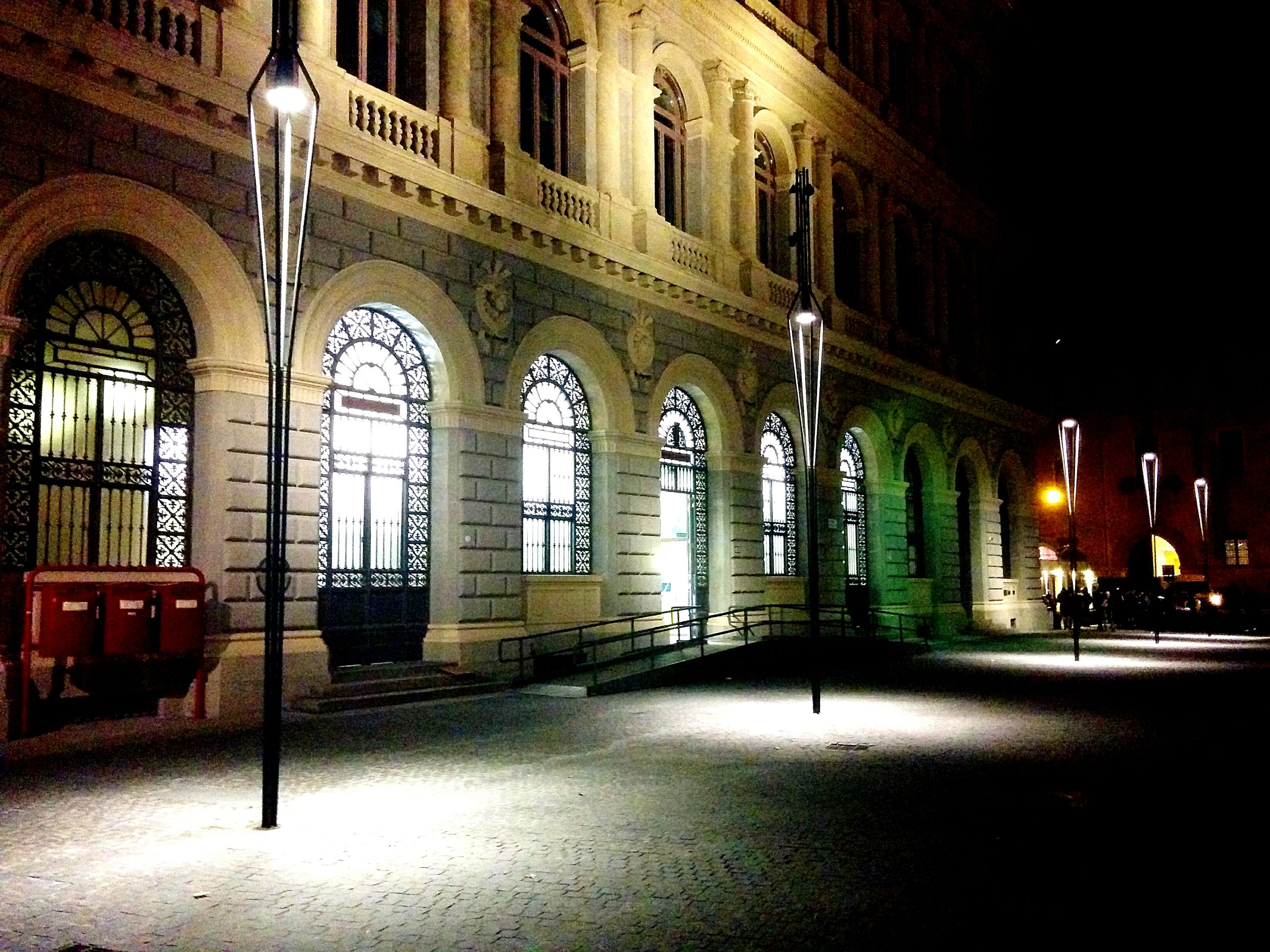 architecture, built structure, building exterior, illuminated, night, street, transportation, arch, city, street light, car, land vehicle, building, road, mode of transport, architectural column, incidental people, outdoors, lighting equipment, no people