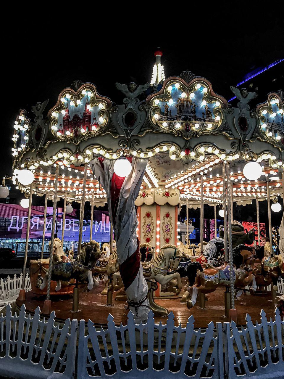 amusement park, amusement park ride, carousel, illuminated, night, representation, animal representation, arts culture and entertainment, leisure activity, carousel horses, mammal, art and craft, horse, animal, animal wildlife, built structure, livestock, enjoyment, group of people, domestic, outdoors, merry-go-round