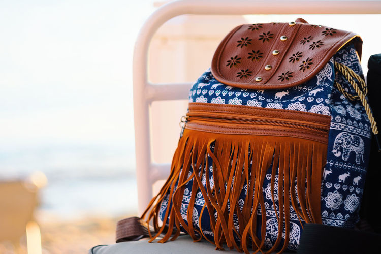 Front View Of Blue Hipster Backpack With White Elephant Pattern And Leather Fringes On Chair By The Beach Blue Wave Copy Space Elégance Hipster Style Holiday Leather Relaxing Retro Vacations Backpack Bag Beach Blue Blue Sky Casual Clothing Close-up Clothing Fringes No People Pattern Rucksack Sea Summer Textile Tourism
