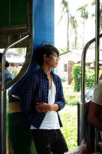 Young man looking away while standing in train