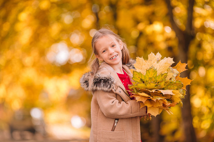 Portrait of smiling girl standing against plants during autumn