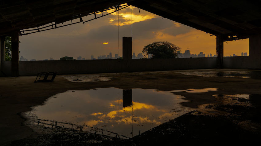 Reflection of a sunset sky on a puddle in an abandoned building Afternoon Dark Pond Abandoned Architectural Column Architecture Building Built Structure City Cloud - Sky No People Old Puddle Quiet Place  Reflection Silhouette Sky Sunset Tree Water The Creative - 2018 EyeEm Awards