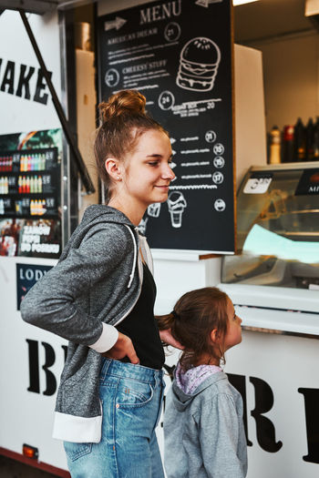Teenage girl and her younger sister waiting for their order at front of a food truck
