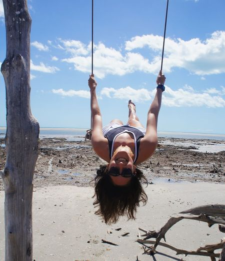 Portrait of smiling woman swinging at beach
