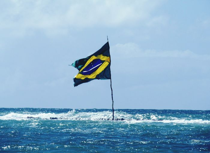 Sea Flag Identity Horizon Over Water Water National Flag Patriotism Blue Sky Scenics Yellow Tranquility Tranquil Scene Waterfront Wave Waving Nature Flag Pole Wind Outdoors