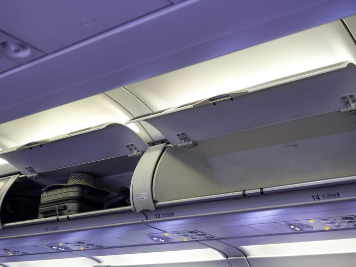 Low angle view of luggage compartment in airplane