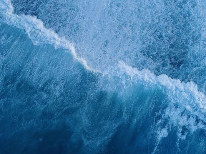 Aerial view of waves splashing in sea