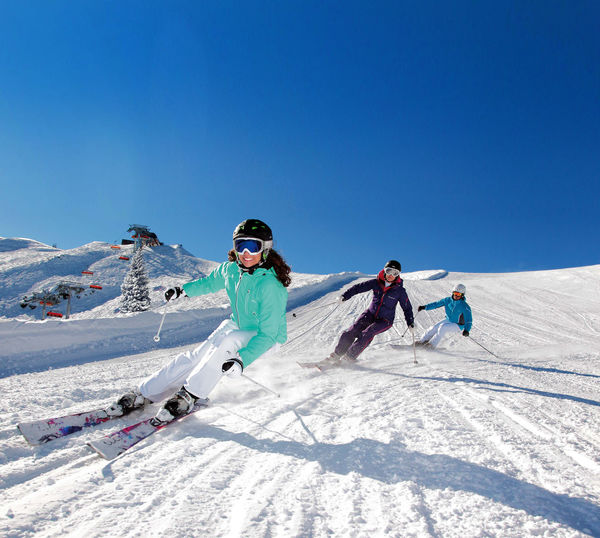 People skiing on snowy mountain against clear blue sky