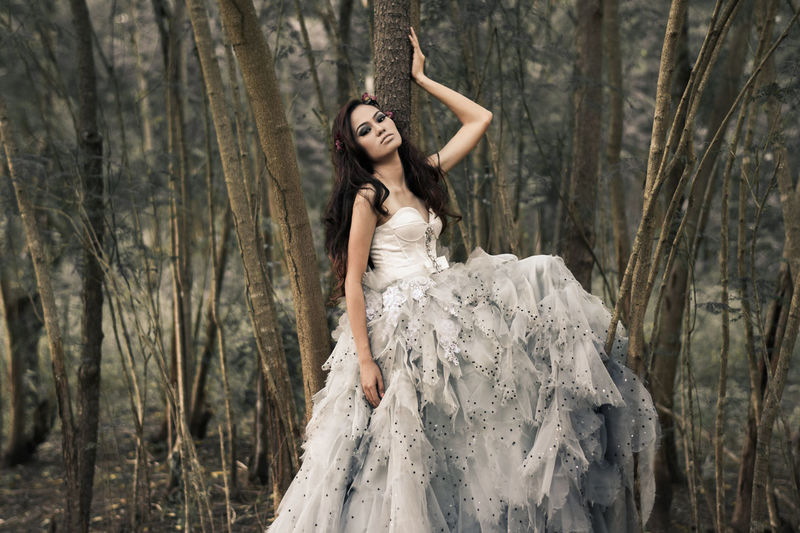 Portrait Of Female Model In White Evening Gown Posing By Trees