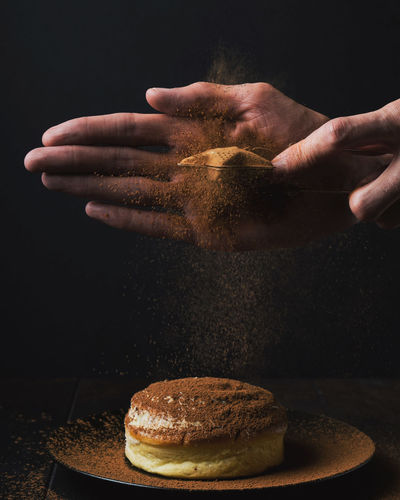 Cropped hands garnishing dessert against black background